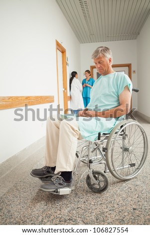 Patient in a wheelchair closing eyes in hospital - stock photo