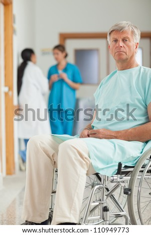 Patient in a wheelchair looking at camera in hospital corridor