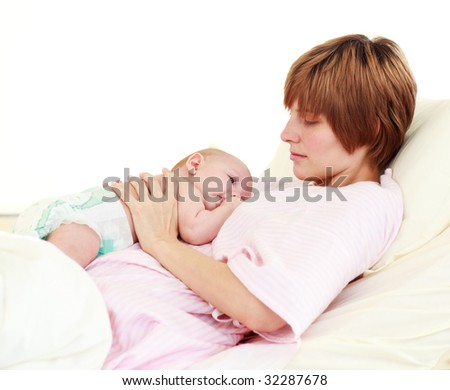 Patient looking at her newborn baby in bed in hospital - stock photo