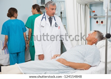 Patient lying in bed in hospital room talking to doctor - stock photo