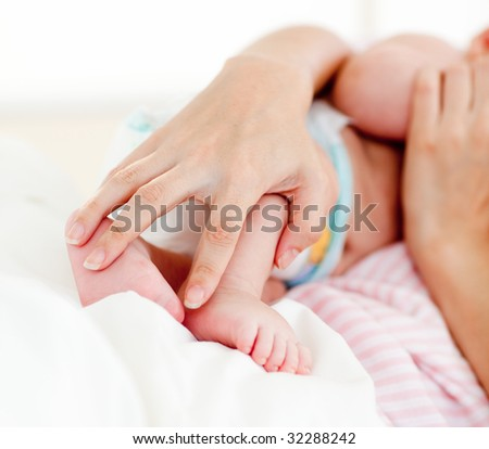 Patient's hands holding a newborn baby in bed in hospital