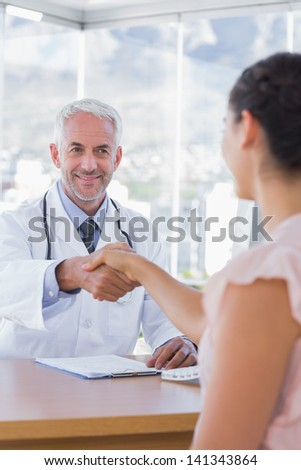Patient shaking hands to doctor in the office at desk - stock photo