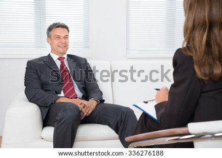 Patient Sitting On Couch In Front Of Female Psychiatrist Writing On Clipboard - stock photo