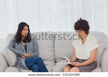 Patient speaking to her therapist while she is taking notes - stock photo