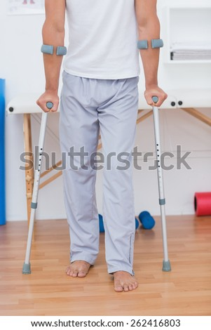Patient standing with crutch in medical office