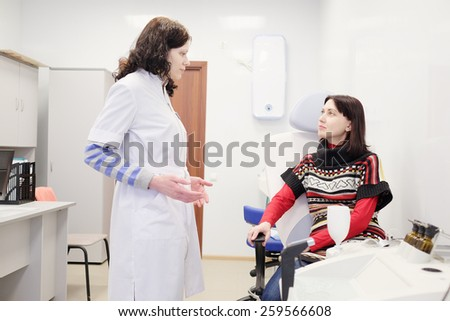 Patient talking to her doctor in examination room  - stock photo