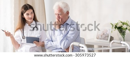 Patient talking with young doctor at home