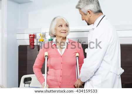 Patient With Crutches Looking At Doctor In Rehab Center