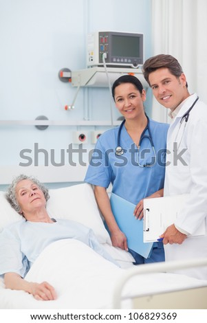 Patient with her doctor and nurse looking at camera in hospital ward