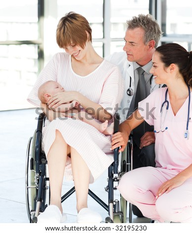 Patient with her newborn baby and doctors in hospital - stock photo