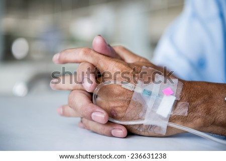 Patient with IV drip in a hospital - stock photo