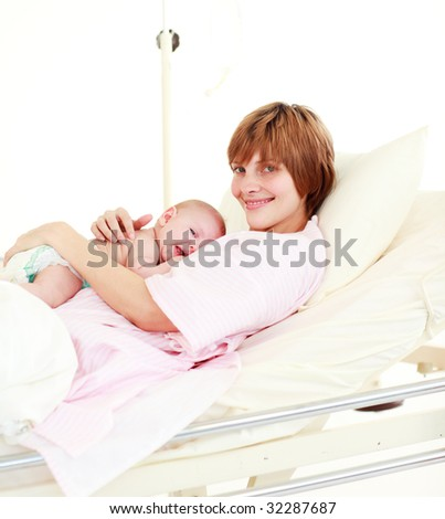 Patient with newborn baby in hospital smiling at the camera
