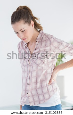 Patient with stomach ache looking at camera in medical office