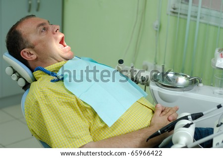 patient with the opened mouth in chair of dentist - stock photo