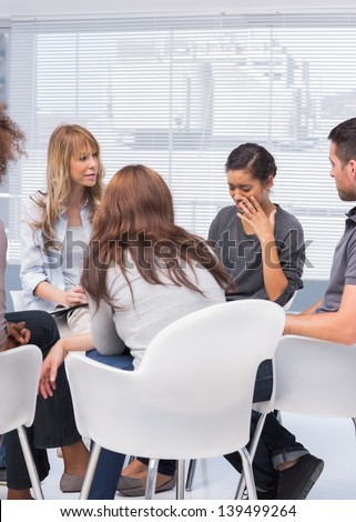 Patients and therapist listening to woman telling her problems - stock photo