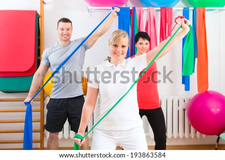 Patients at the physiotherapy doing physical exercises with therapist - stock photo