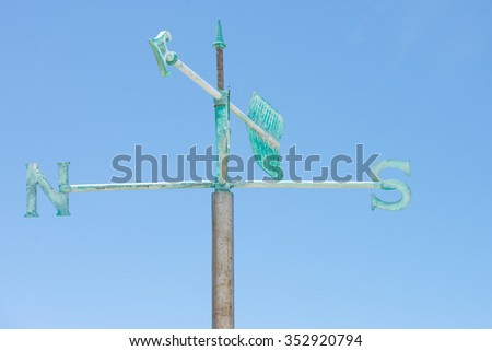 Patina green rusty old weather vane isolated on summer sunny blue sky background, with pointing arrow and symbols for direction, copy space. - stock photo