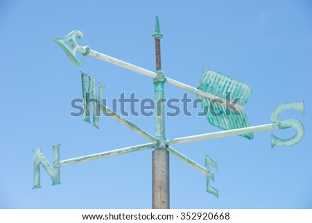 Patina green rusty old weather vane on pole isolated on summer sunny blue sky background, with pointing arrow and symbols for direction, copy space. - stock photo