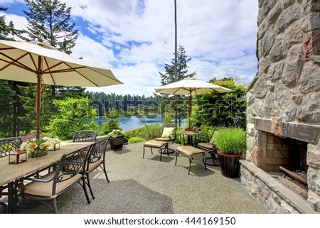 Patio area with stone fireplace, concrete floor, patio table set and deck chairs.