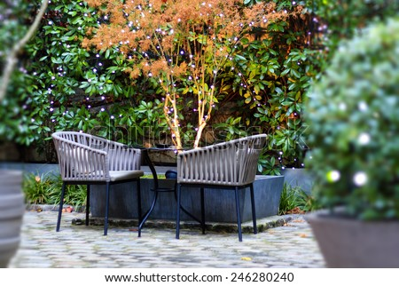 Patio table and chairs in the Christmas decorated garden with garlands on the plants. - stock photo