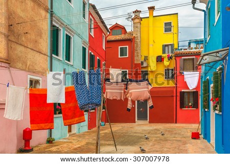 Patio with colorful houses with laundry drying on a rope on the famous island Burano, Venice, Italy