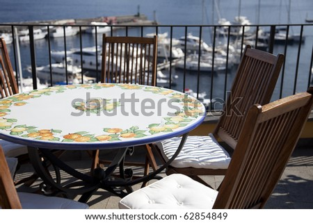 Patio with table and chair, above the marin has beautiful view of port. - stock photo