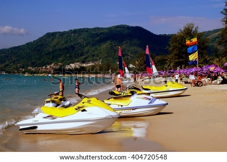 Patong / Phuket, Thailand - January 9, 2007:  Catamarans with large sails and rental jet ski boats sitting on sandy Patong Beach
