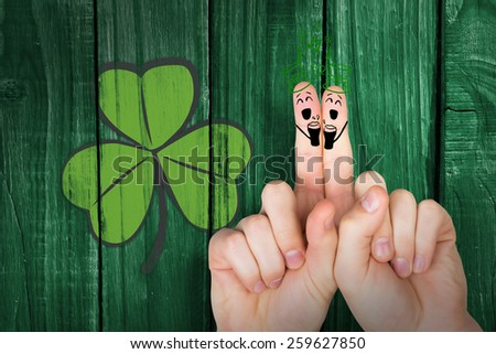 Patricks Day fingers against green wooden background - stock photo