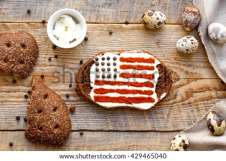 Patriot breakfast - sandwich with image of american flag on wooden table. Top view.