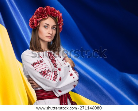 Patriotic concept. Beautiful girl in the Ukrainian national suit against Ukrainian flag background  with copy space  - stock photo
