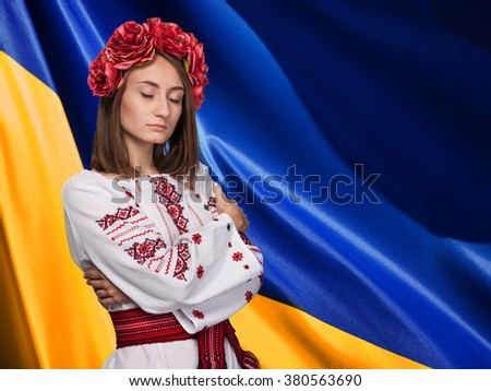 Patriotic concept.  Beautiful girl with closed eyes in the Ukrainian national suit against Ukrainian flag background
