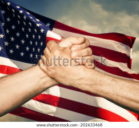 Patriotic concept. Handshaking. The USA flag and shaking hands of two male people - stock photo