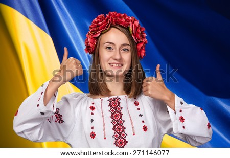 Patriotic concept. Happy young girl in the Ukrainian national suit against Ukrainian flag background