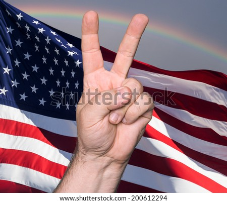 Patriotic concept.  Man hand showing the sign of victory and peace against of USA flag  - stock photo