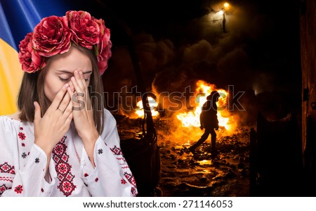 Patriotic concept. Sorrowful beautiful young girl in Ukrainian national suit covers her face with her hands against Ukrainian flag background
