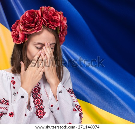 Patriotic concept. Sorrowful beautiful young girl in Ukrainian national suit covers her face with her hands against Ukrainian flag background - stock photo