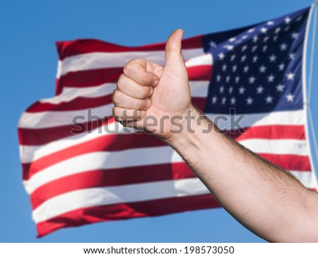 Patriotic concept. Thumb up sign against of United States of America flag