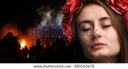 Patriotic concept. Ukraine in fire. Close-up portrait of beautiful crying girl with tears on her cheeks against the background of mass riots