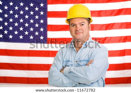 Patriotic construction worker standing in front of an American flag.  Photographed in front of flag, not composite image. - stock photo