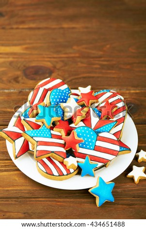 Patriotic cookies for 4th of July on a wooden background in a white plate. With scattered stars. Vertical shot - stock photo