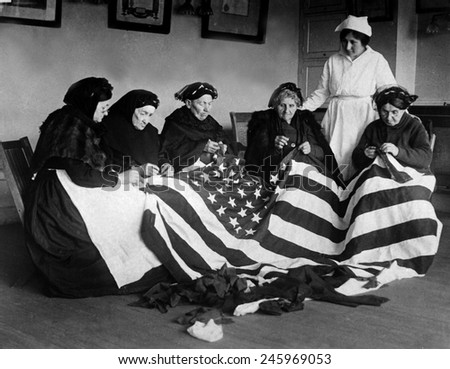 Patriotic elderly immigrant women making a flag during WWI. They are from Eastern Europe countries of Hungary, Galicia, Russia, Germany, and Rumania. Ca. 1918.