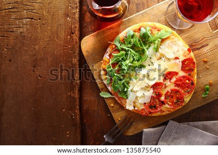 Patriotic Italian tricolore pizza with stripes of red, white and green in the colours of the national flag formed by tomato, cheese and fresh rocket leaves used for the topping on a wooden table . - stock photo