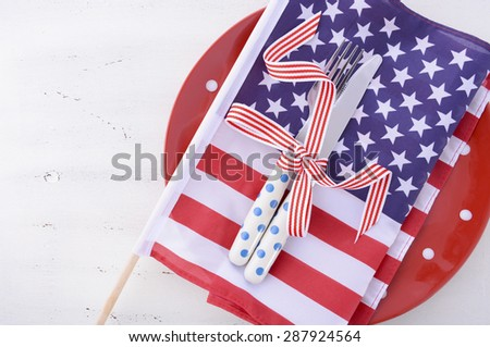 Patriotic table place setting with USA flag and polka dot plate on white wood shabby chic table for Fourth of July and USA holiday and events celebration.