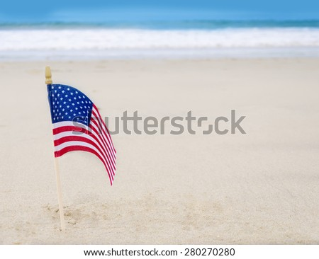 Patriotic USA background with American flag on the sandy beach - stock photo
