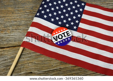 patriotic vote pin on an American flag on rustic wood background