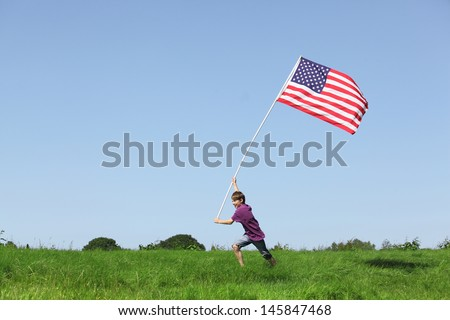 Patriotic young boy running with a american flag on grenn meadow - stock photo