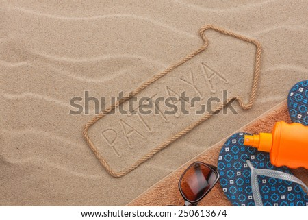 Pattaya  pointer and beach accessories lying on the sand, as background - stock photo