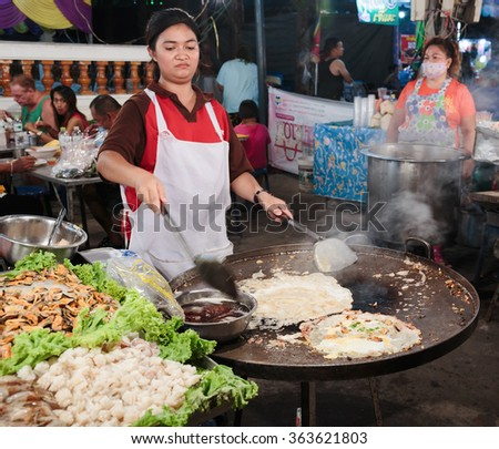 PATTAYA, THAILAND - APRIL 4, 2015: Woman in a street cafe fry food