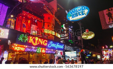 PATTAYA, THAILAND - FEBRUARY 18, 2016: multicolored neon signs and blurred people on the new Walking Street of the city - The road is closed to the traffic after 6pm and stays crowded until late night