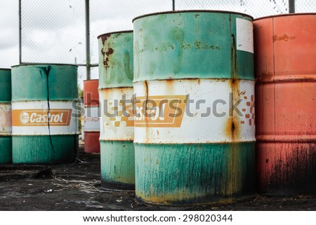 PATTAYA,THAILAND - JULY 20, 2015: The rusty oil barrel set in dirty floor in store of factory in Pattaya